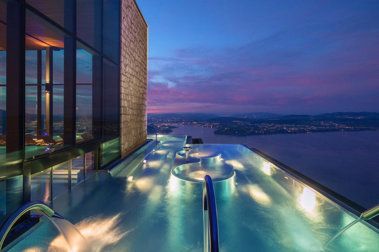The infinity pool at the Bürgenstock Alpine Spa just after sunset